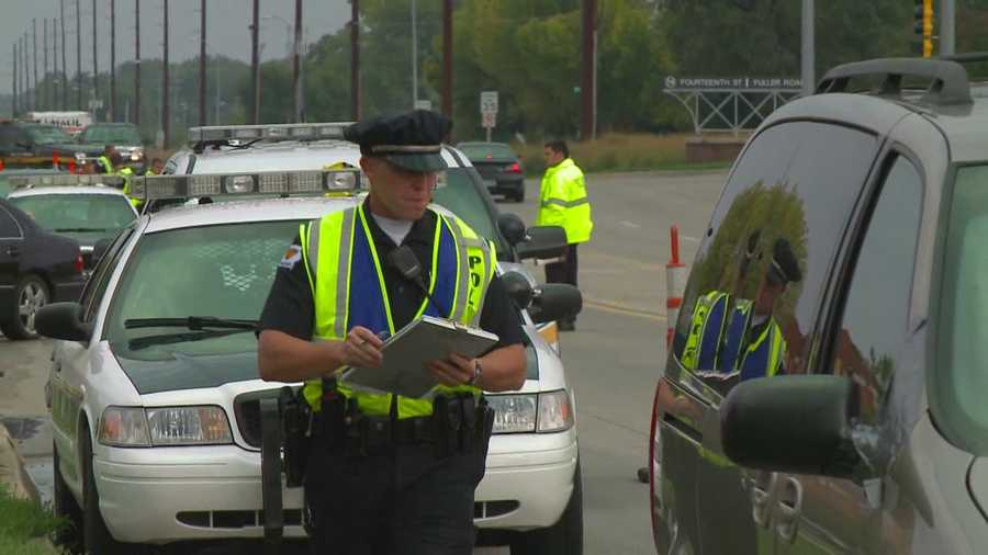 Officers conduct safety checks on cars in West Des Moines on Oct. 4.
