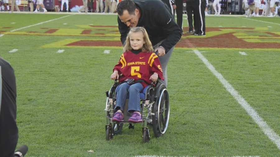 "In a touching timeout, a quarterback from the opposing team talks to an enthusiastic Iowa State ""kid captain."""