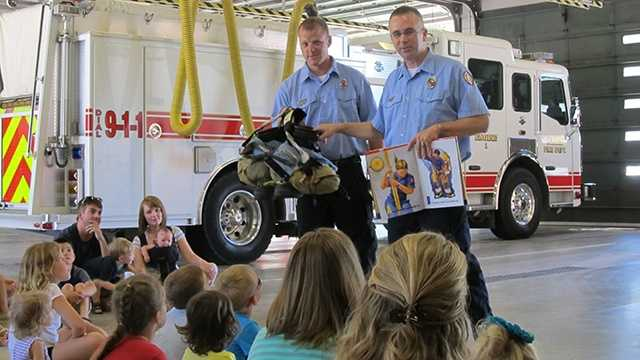 "Firefighter Todd Moomaw, right, reads ""Firefighters A to Z,"" with help from Firefighter Jess Bappe."