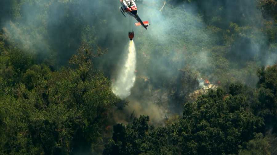See images from LiveCopter3 of fire crews battling a brush fire that crept close to homes near Oakdale.