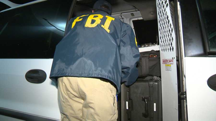 Agents from the FBI and Immigration and Customs Enforcement seize computers, files, and other materials from the offices of Americans Helping America Chamber of Commerce on Dec. 22, 2015.