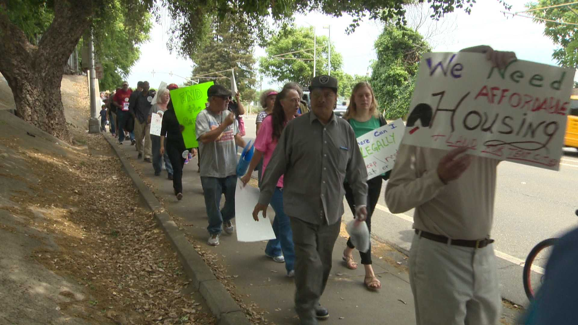 Homeless people and their supporters march along 12th Street in Sacramento.