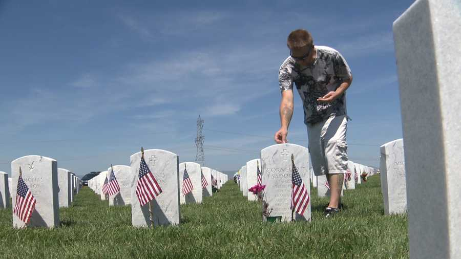 Army veteran Christopher Wright puts pennies on fallen heroes' tombstones in the Sacramento Valley National Cemetery on Monday, May 30, 2016.