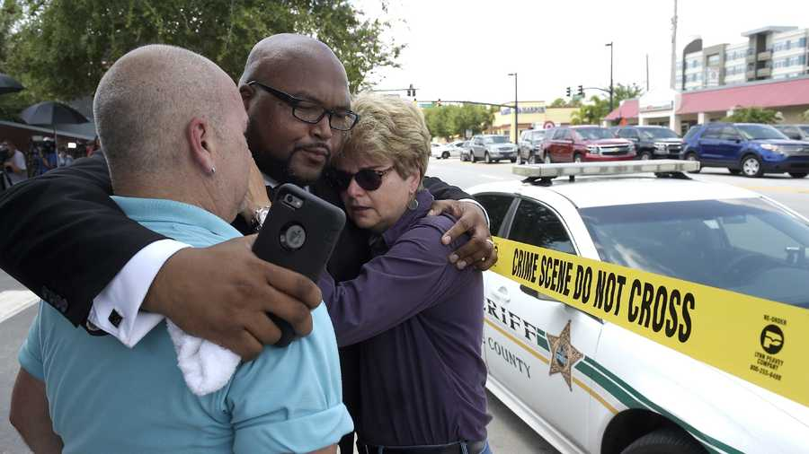 Terry DeCarlo, executive director of the LGBT Center of Central Florida, left, Kelvin Cobaris, pastor of The Impact Church, center, and Orlando City Commissioner Patty Sheehan console each other after a shooting involving multiple fatalities at a nightclub in Orlando, Fla., Sunday, June 12, 2016.