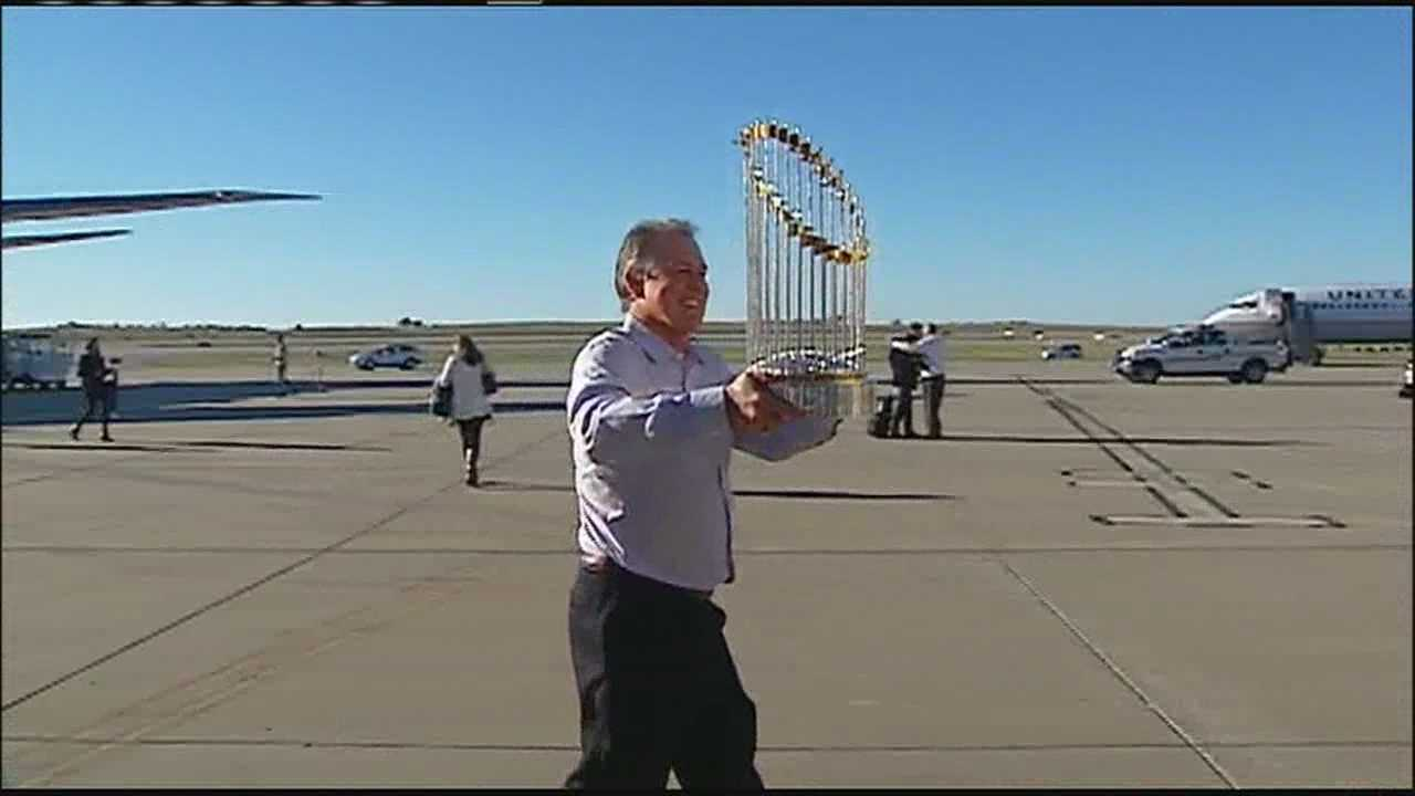 Royals manager Ned Yost hoists the World Series trophy as he left the plane carrying the team back from New York.