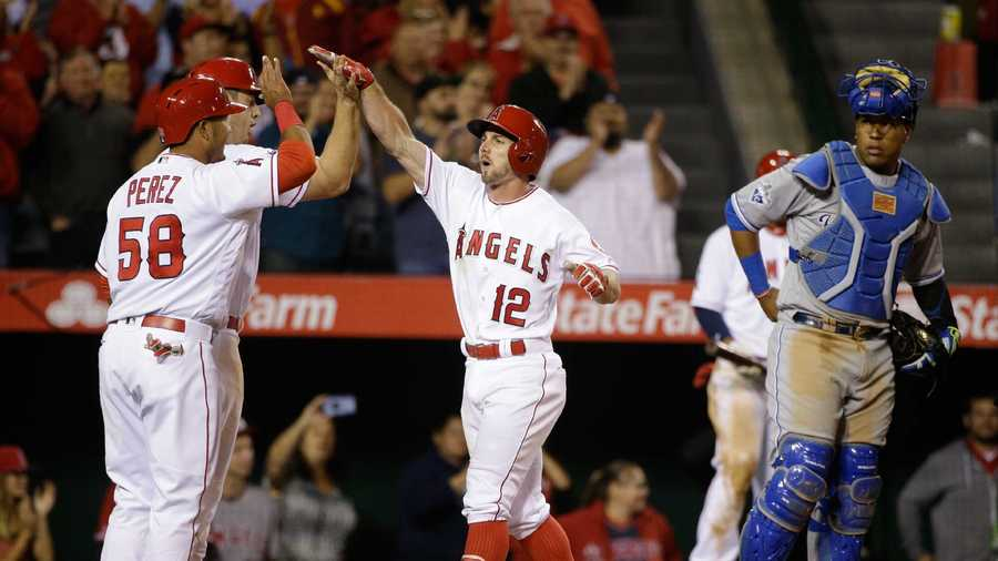 Los Angeles Angels' Johnny Giavotella, center, celebrates his three-run home run with Carlos Perez, front left, and C.J. Cron as Kansas City Royals catcher Salvador Perez, right, waits during the fifth inning of a baseball game Tuesday, April 26, 2016, in Anaheim, Calif. (AP Photo/Jae C. Hong)