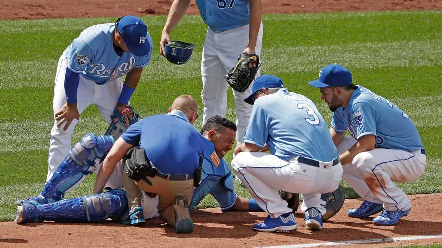Kansas City Royals catcher Salvador Perez, center, is tended to after a collision following his catch of a fly foul ball for the out on Chicago White Sox's Adam Eaton during the ninth inning of a baseball game Saturday, May 28, 2016, in Kansas City, Mo. The Royals won 8-7. (AP Photo/Charlie Riedel)
