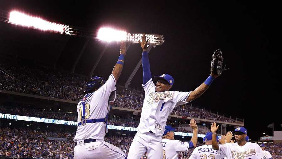 Kansas City Royals' Jarrod Dyson (1) and Salvador Perez (13) celebrate after the Royals defeated the Texas Rangers 3-1 in a baseball game Friday, July 22, 2016, in Kansas City, Mo. (AP Photo/Charlie Riedel)