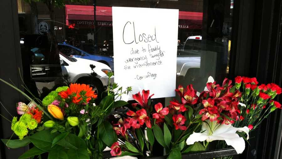 "Flowers were left on the front door of Camouflage, a shop in downtown Santa Cruz. A note on the door reads, ""Closed due to family emergency."""