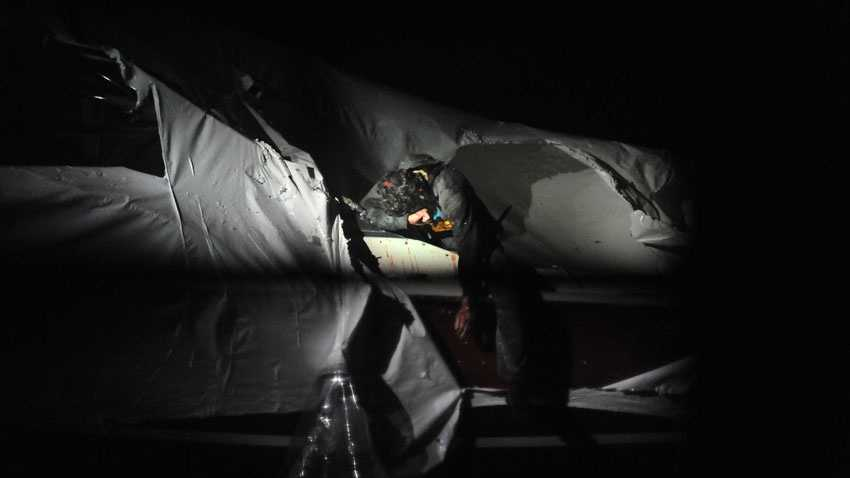 Boston Marathon bombing suspect Dzhokhar Tsarnaev slumps across the deck of the trailered boat the night he was found and captured.
