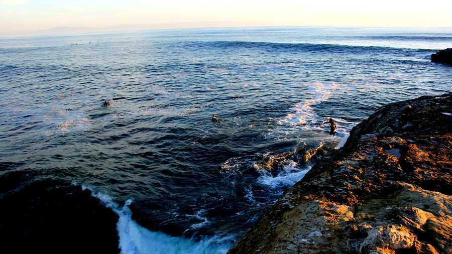Three surfers jump off a cliff at Steamer Lane in Santa Cruz late Sunday afternoon.