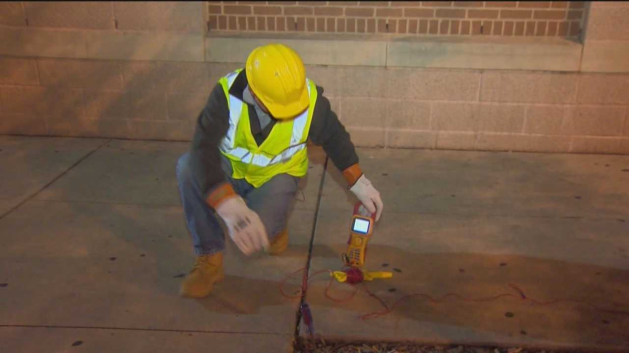 A Power Survey workers notices voltage in a sidewalk in Pigtown.