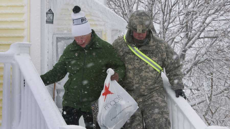 Sgt. Thomas Jones, 35, from Plymouth, Mass., a Squad leader with the 10-58th Transportation Company out of Hingham, helps a citizen of Hull, who lost power the night of the storm, out of her house.