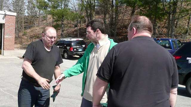 James Christian (L)  reaches to shake Guy Leboeuf's hand, as police detective James Hoover watches.