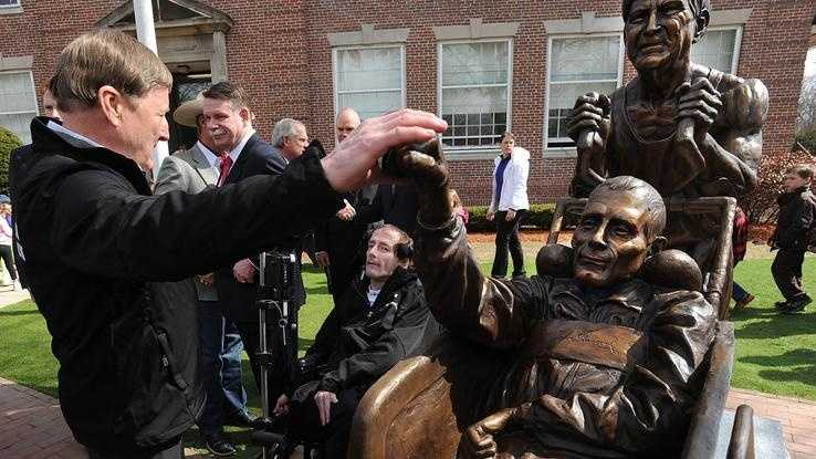 Dick Hoyt pats his son's bronze outstretched fist during the Dick and Rick Hoyt statue unveiling ceremony in front of the Center School in Hopkinton.