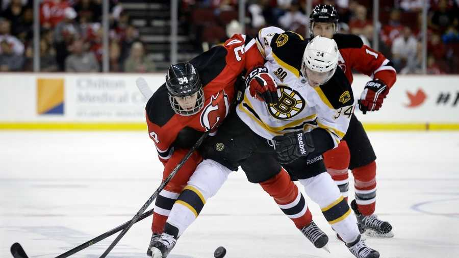Boston Bruins' Carl Soderberg, front right, of Sweden, and New Jersey Devils' Jon Merrill, front left, battle over the puck during the first period of an NHL hockey game in Newark, N.J., Sunday, April 13, 2014. (AP Photo/Mel Evans)