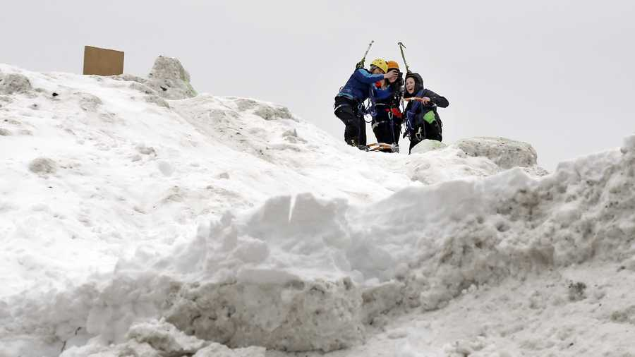 "Three students from the Massachusetts Institute of Technology take a selfie after jokingly using mountaineering gear to make their way up a massive snow pile on the MIT campus in Cambridge, Mass., Wednesday, Feb. 18, 2015. The mountain of excess snow has been dubbed the ""Alps of MIT"" and is being used for climbing, sledding and posing."