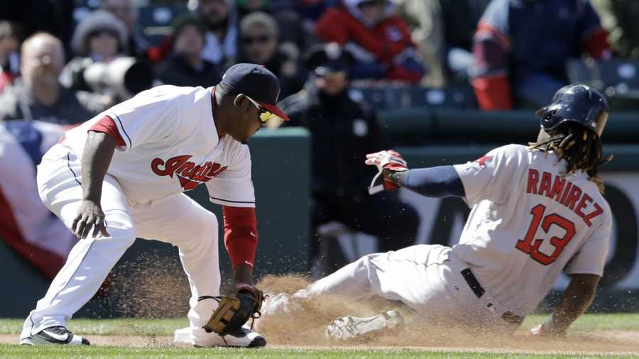 Boston Red Sox' Hanley Ramirez (13) slides safely into third base as Cleveland Indians' Juan Uribe (4) is late on the tag in the sixth inning of a baseball game, Tuesday, April 5, 2016, in Cleveland. Ramirez advanced to third base on a single by Travis Shaw.
