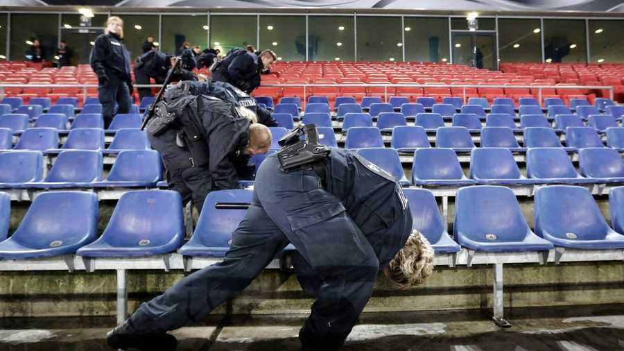 German police officers search between the seats of the stadium prior to an international friendly soccer match between Germany and the Netherlands in Hannover, Germany, Tuesday, Nov. 17, 2015 following Friday's attacks in Paris