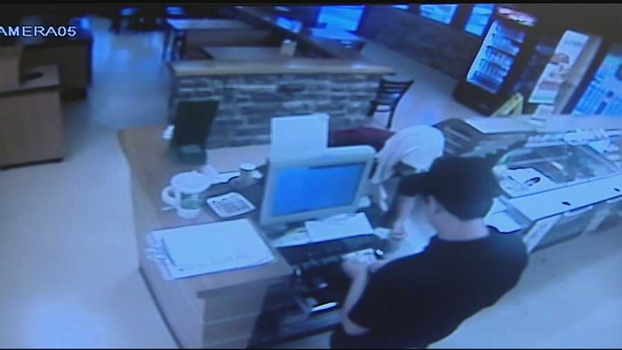 In the surveillance video, a man with a red shirt, black pants, and a towel over his head can be seen handing the clerk change to pay for a soda. When the drawer is open, he pulls a knife from his pocket and leaves with everything in the register.