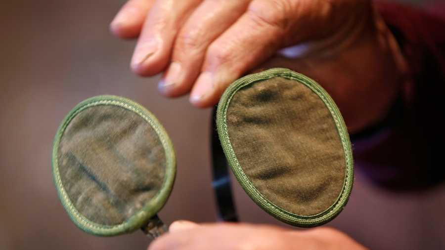 "In this December 2015 photo, a pair of old drab olive-colored ear protectors commissioned by the U.S. Army is held in Farmington, Maine. The town of Farmington celebrate the earmuff inventor on ""Chester Greenwood Day"" with a parade on Saturday, Dec. 5."