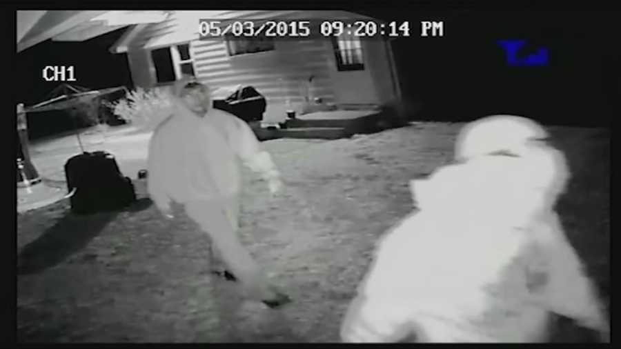 Investigators have released surveillance video of a home invasion in Charlestown in which two men rushed at a woman as she opened the door to let her dog in.