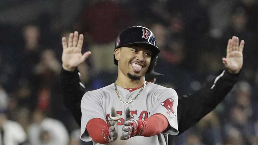 Boston Red Sox's Mookie Betts reacts toward David Ortiz, left, and third base coach Brian Butterfield, right, after hitting a two-run double during the eighth inning of a baseball game against the New York Yankees Wednesday, Sept. 28, 2016, in New York.