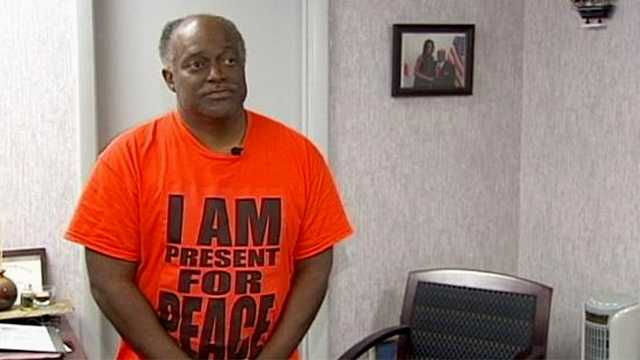 "Riviera Beach Mayor Thomas Masters shows off his T-shirt that reads ""I Am Present For Peace."""