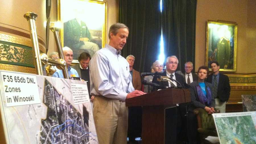 Primary care physician John Reuwer speaking at a Statehouse news conference. Rep. George Cross appears at right.