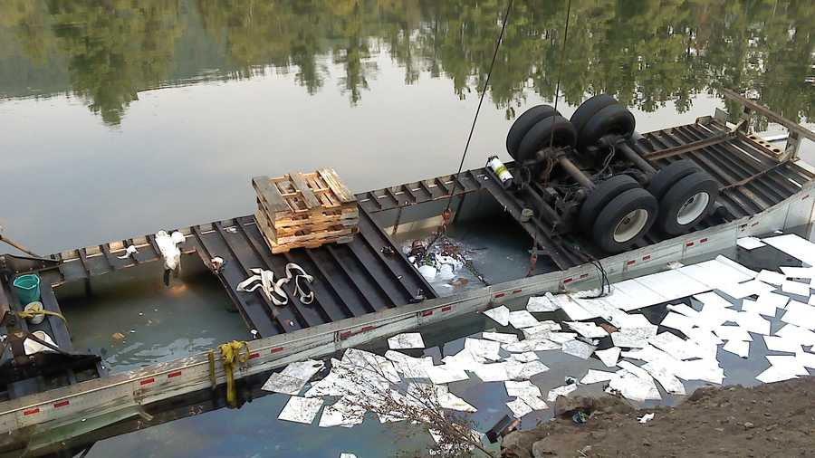 The tractor trailer that went off of the Winooski River Bridge of Interstate 89, near Exit 15, is submerged in the river below.