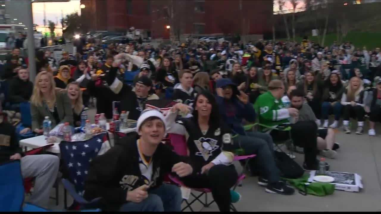 Hockey fans gather to watch a Penguins game on a big screen outside the arena.