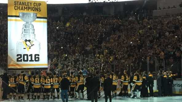 The Pittsburgh Penguins gather to watch their fourth Stanley Cup banner raise over the ice.