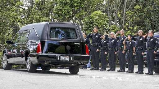 Los Angeles police officers salute as a hearse leaves the home of Nancy Reagan in the Bel-Air district of Los Angeles.