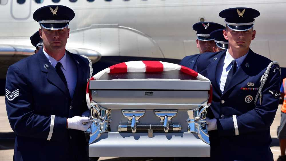 A U.S. Air Force Honor Guard team transfers the remains of Staff Sgt. Robert Dale Van Fossen, of Greenbrier, Ark.