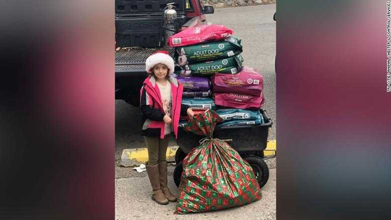 Landyn Wadsworth, 8, stands next to her Christmas present -- 600 pounds of pet food for a local shelter.