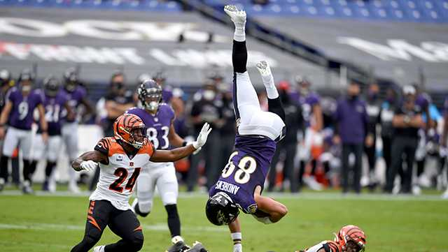 Ravens Mark Andrews flips over after making a completion against the Bengals
