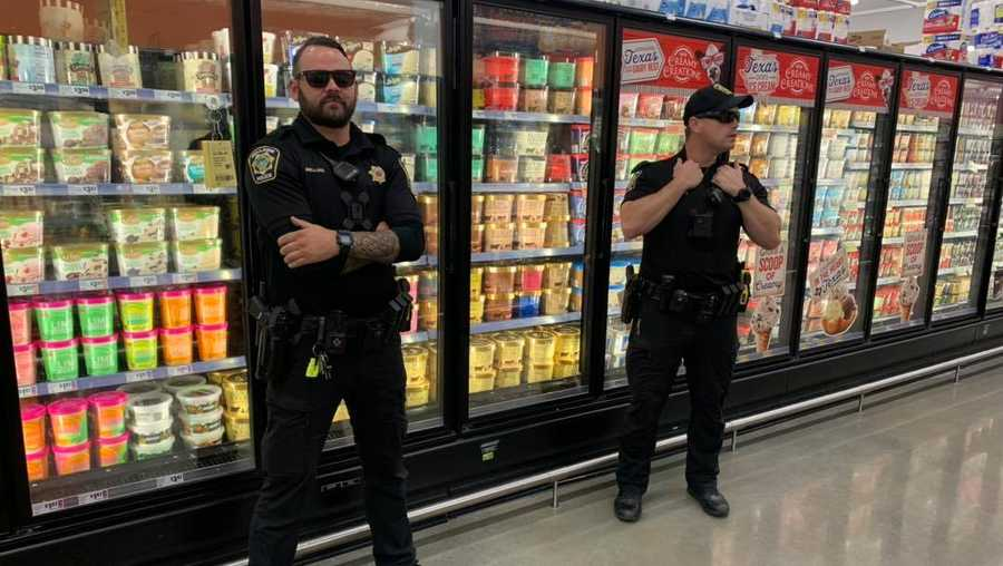 Officers stand in front of ice cream aisle