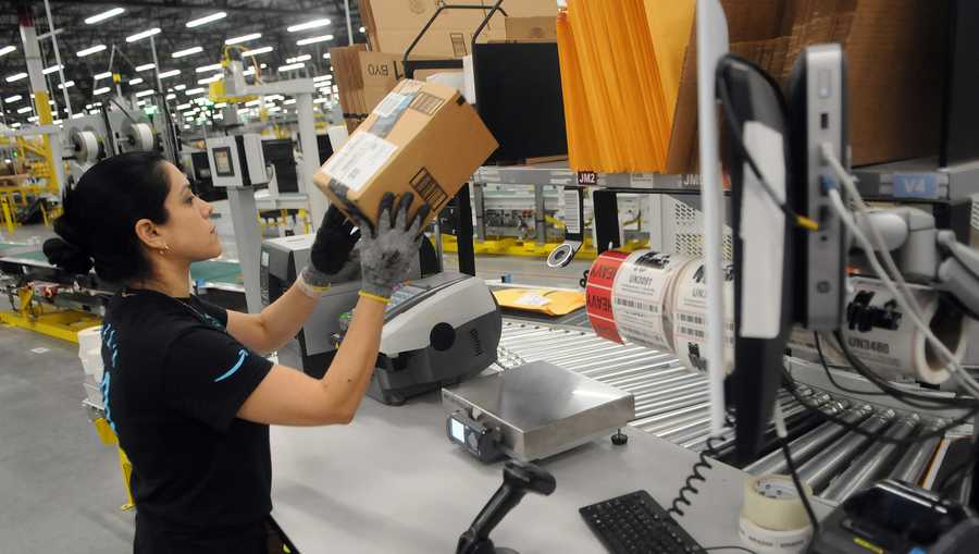 An Amazon associate processes a package for delivery at the newest Amazon Robotics fulfillment center during its first public tour on April 12, 2019 in the Lake Nona community of Orlando, Florida.