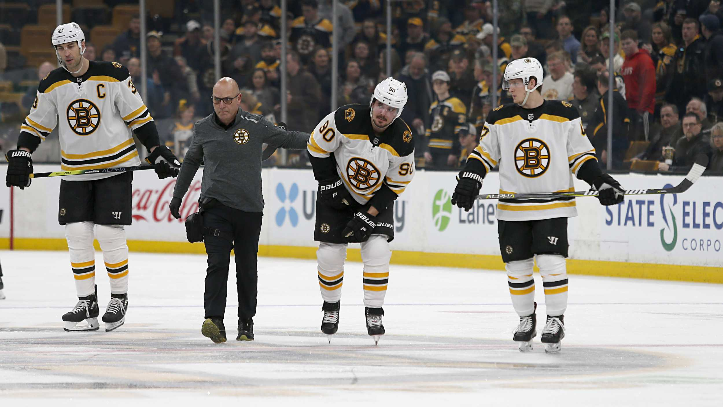 A trainer helps Boston Bruins left wing Marcus Johansson (90) off the ice after he was injured as Zdeno Chara, left, and Torey Krug, right, look on during the first period of an NHL hockey game against the Carolina Hurricanes, Tuesday, March 5, 2019, in Boston. (AP Photo/Mary Schwalm)