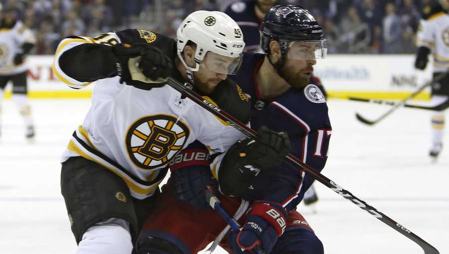 Boston Bruins' Matt Grzelcyk, left, and Columbus Blue Jackets' Brandon Dubinsky chase a loose puck during the second period of Game 3 of an NHL hockey second-round playoff series Tuesday, April 30, 2019, in Columbus, Ohio. (AP Photo/Jay LaPrete)