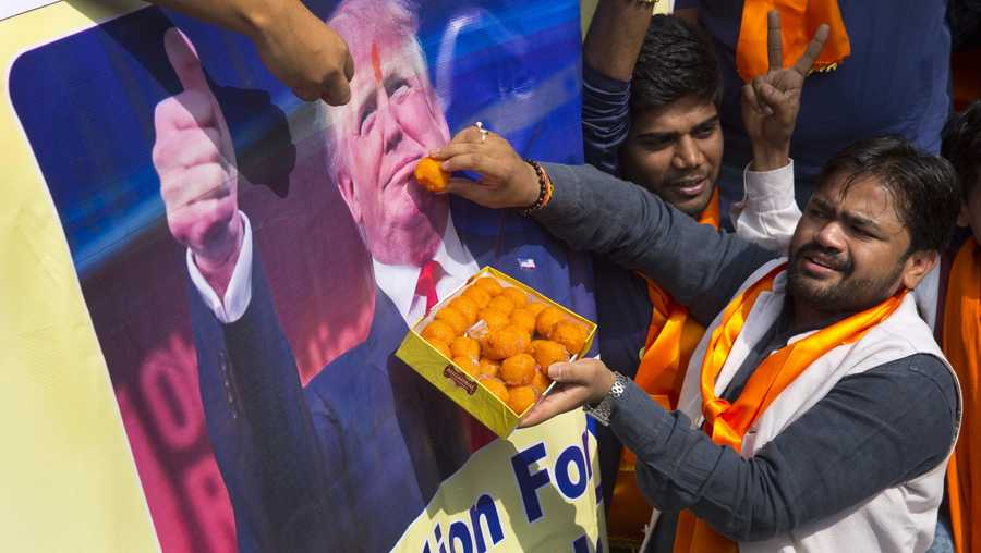 Activists belonging to 'Hindu Sena' or Hindu Army, a local organization offer sweets symbolically to US presidential candidate Donald Trump's poster in anticipation of his victory in New Delhi, India, Wednesday, Nov. 9, 2016.