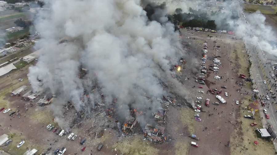 This image made from video provided by APTN, shows a view from a drone of smoke billowing from the San Pablito Market, where an explosion ripped through a fireworks market in Tultepec, Mexico, Tuesday, Dec. 20, 2016.