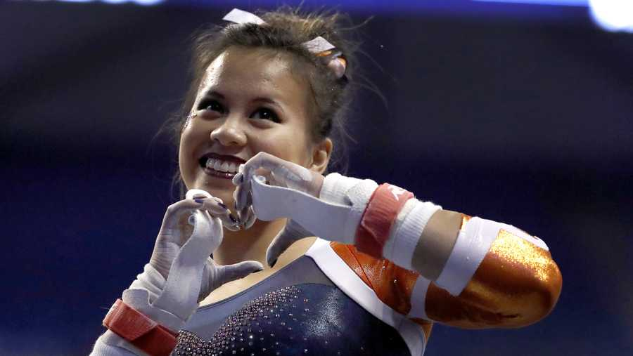 Auburn's Samantha Cerio smiles and signals to the crowd before competing on the uneven parallel bars during the NCAA college women's gymnastics championships Friday, April 14, 2017, in St. Louis. (AP Photo/Jeff Roberson)