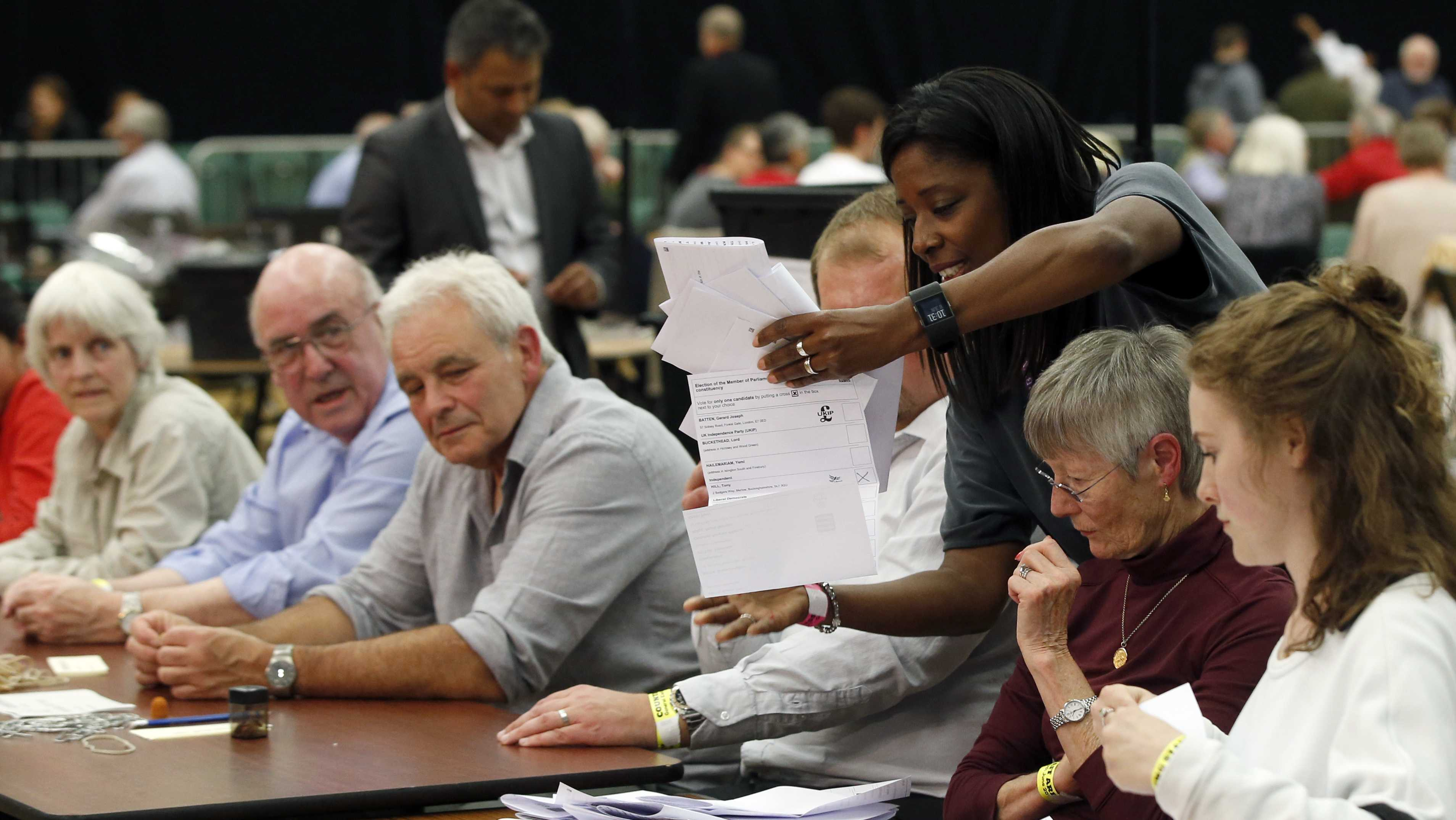 Members of the election staff prepare to count ballots, in the Magnet Leisure Centre Maidenhead, the constituency of Prime Minister Theresa May, in Maidenhead, England, Thursday, June 8, 2017. An exit poll has projected that Prime Minister Theresa May's Conservative Party will win the biggest share of seats in Britain's Thursday election but could fall short of a majority in Parliament.