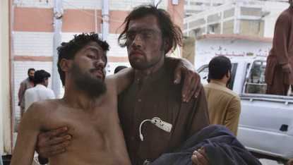 A Pakistani mine worker carries an injured colleague upon arrival at a hospital in Quetta, Pakistan, Saturday, May 5, 2018.