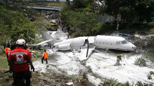 A white Gulfstream jet that appears broken in half near the center, lies engulfed in foam sprayed by firefighters, in Tegucigalpa, Honduras, Tuesday, May 22, 2018.