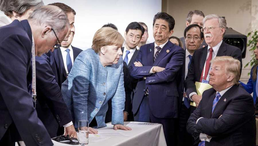 In this photo made available by the German Federal Government, German Chancellor Angela Merkel, center, speaks with U.S. President Donald Trump, seated at right, during the G7 Leaders Summit in La Malbaie, Quebec, Canada, on Saturday, June 9, 2018.