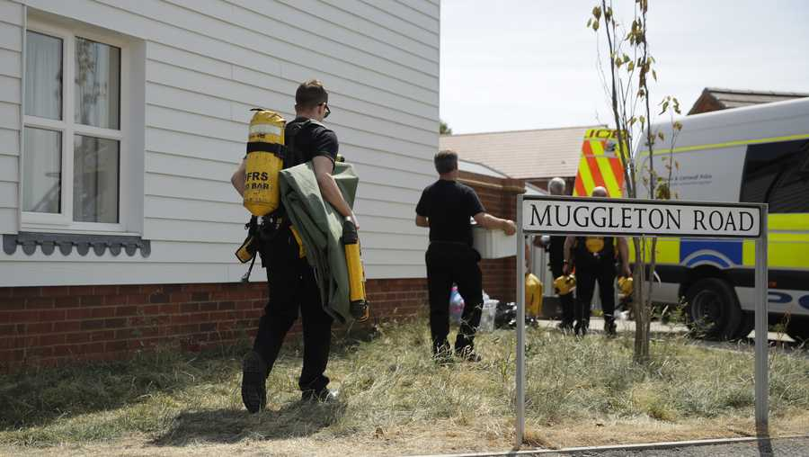 British firefighters carry equipment towards a property being searched on Muggleton Road in Amesbury, England, Friday, July 6, 2018. British police are scouring sections of Salisbury and Amesbury in southwest England, searching for a container feared to be contaminated with traces of the deadly nerve agent Novichok.