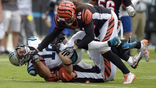 Carolina Panthers' DJ Moore (12) is tackled by Cincinnati Bengals' Clark Harris (46) during the second half of an NFL football game in Charlotte, N.C., Sunday, Sept. 23, 2018. (AP Photo/Mike McCarn)