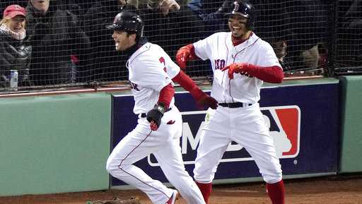 Boston Red Sox's Andrew Benintendi, left, and Mookie Betts celebrate after both scored during the fifth inning in Game 2 of the World Series.